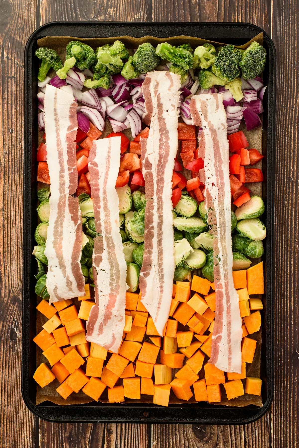 Vegetables on a sheet pan with slices of bacon on top.