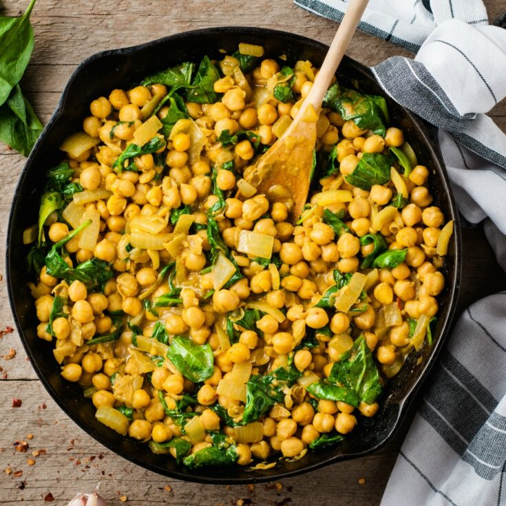 Chickpea curry with spinach in cast iron skillet.