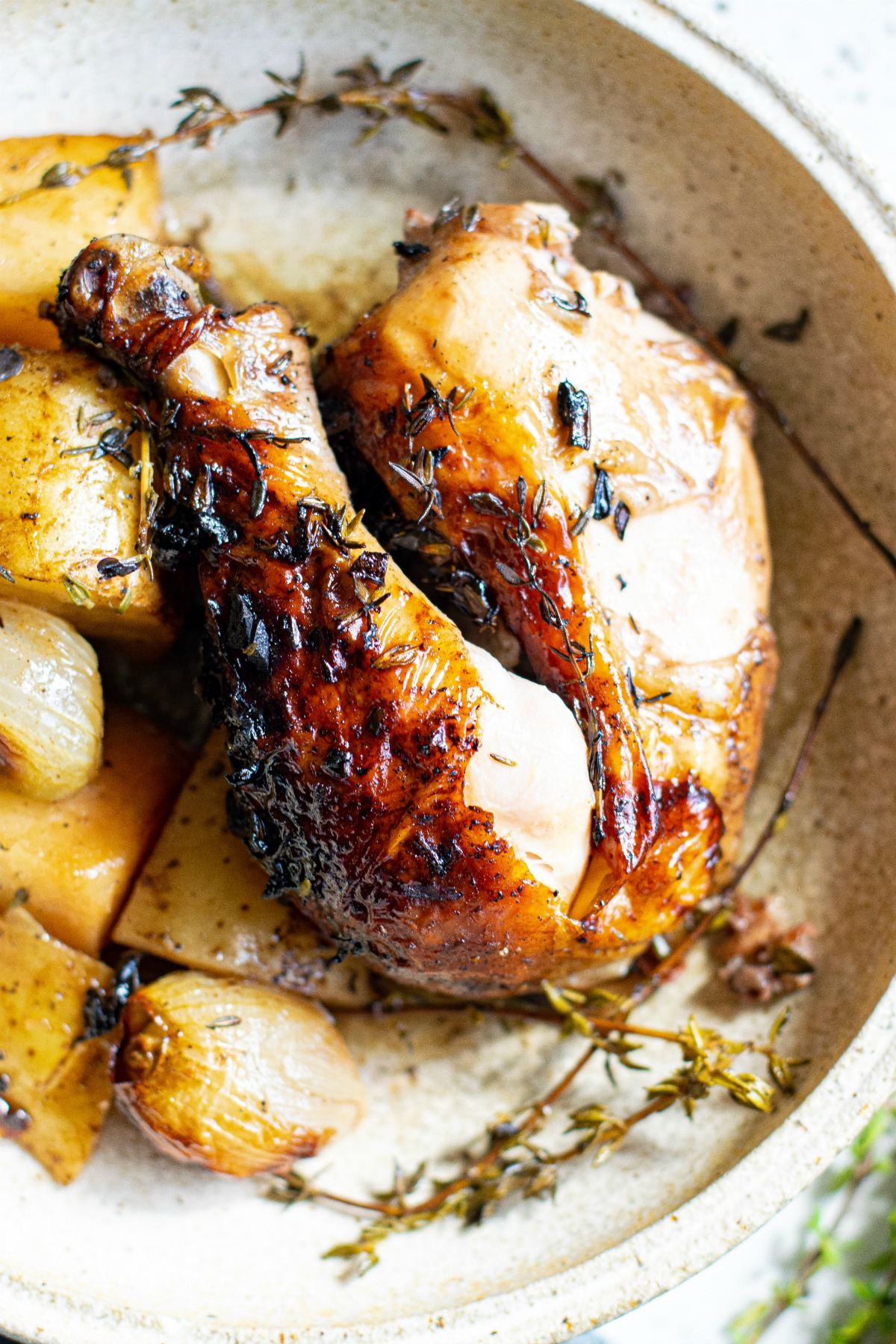 Balsamic chicken leg on plate with potatoes.
