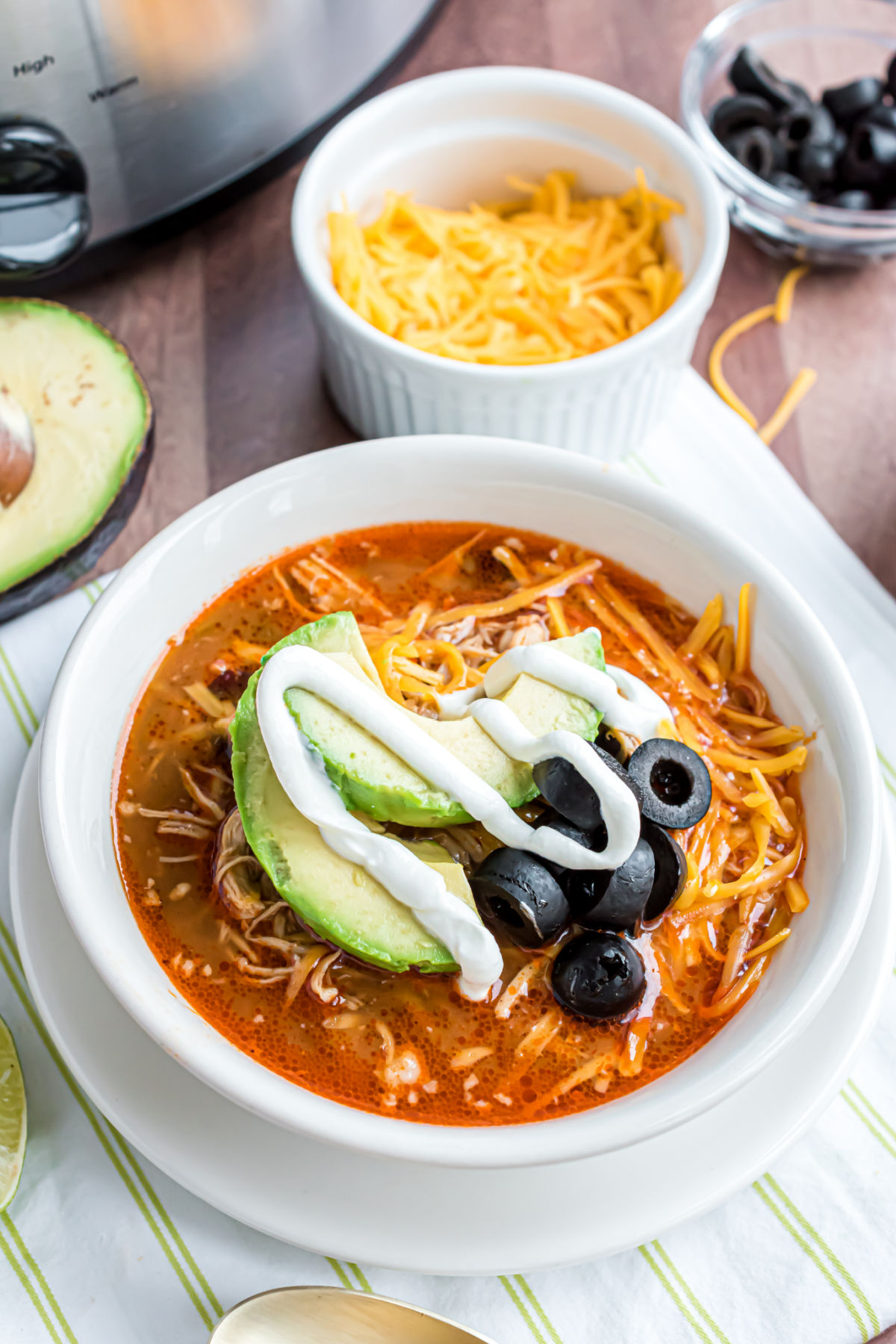 Bowl of chicken enchilada soup garnished with olives, avocado, and sour cream.