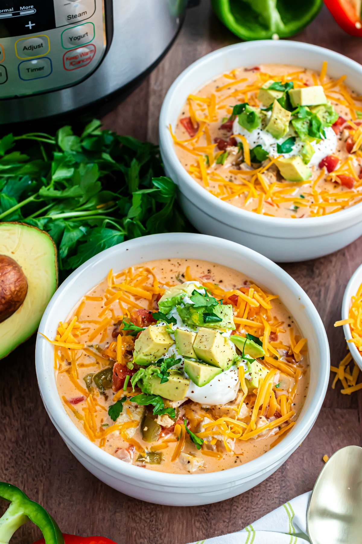 Two bowls of chicken fajita soup with sour cream, avocado and cilantro garnish.