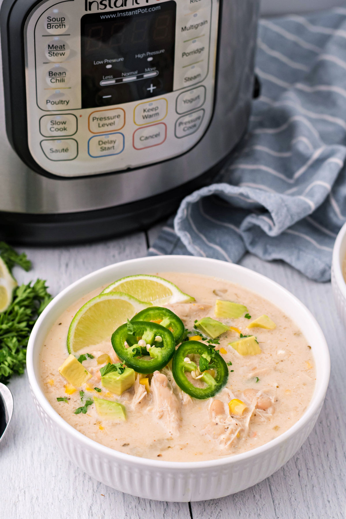 White chicken chili garnished with lime and jalapenos made in the pressure cooker.