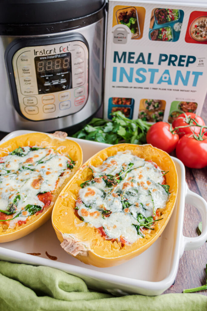 Spaghetti squash lasagna boats with cookbook and instant pot in background.