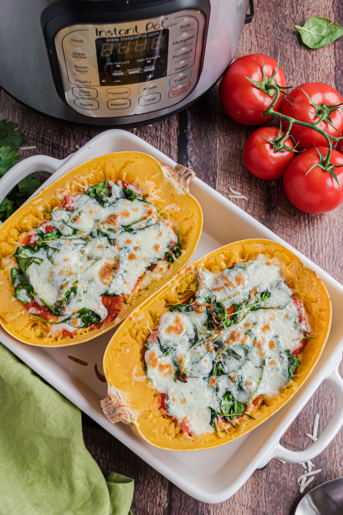 Spaghetti squash halves in a baking dish topped with melted cheese.