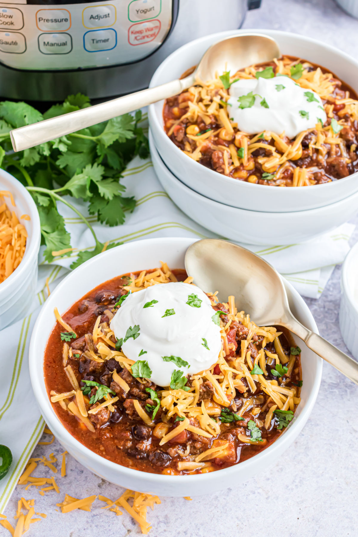 Taco chili served in a bowl with cheese, sour cream, and cilantro.