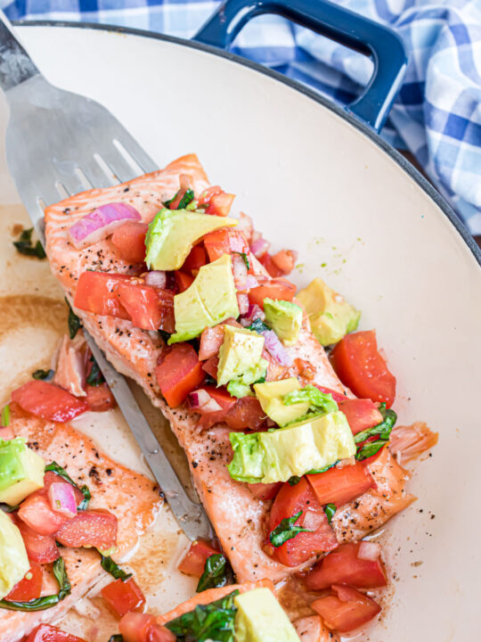 Bruschetta and avocado on a baked salmon filet.