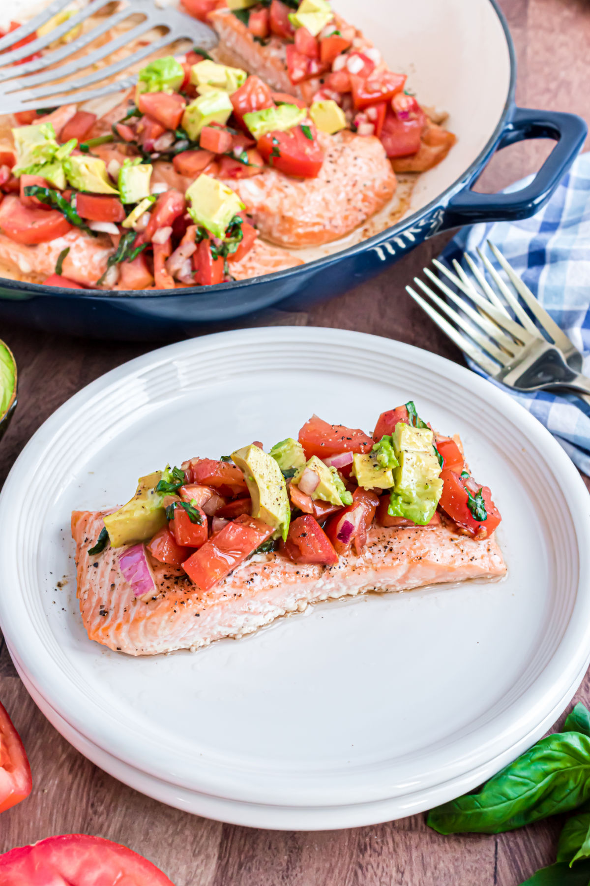 Salmon filet topped with bruschetta and avocado on a white dinner plate.