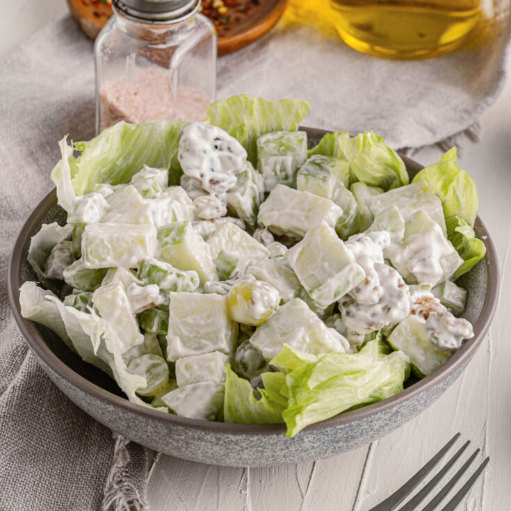 Waldorf salad in a bowl lined with lettuce.