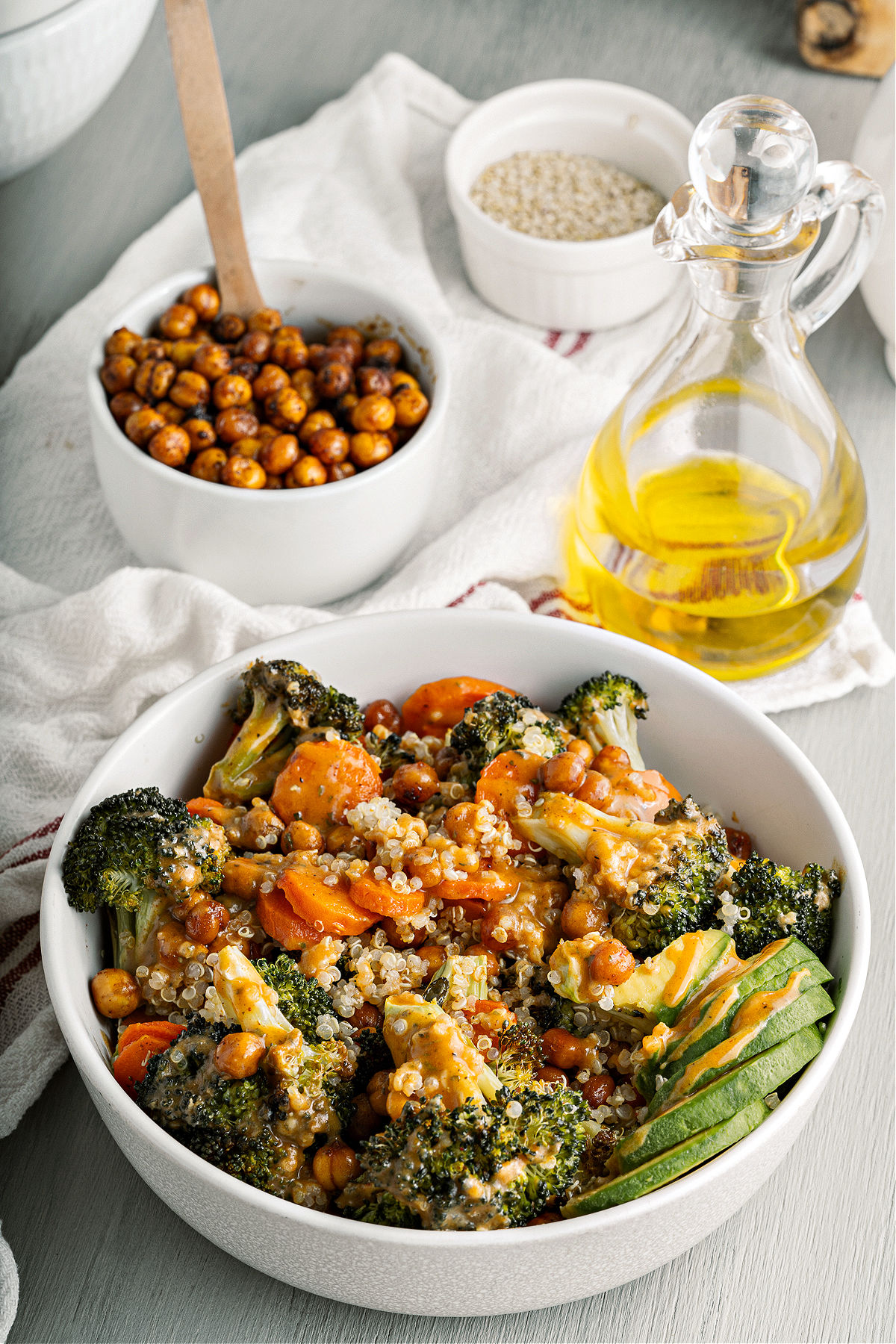 Broccoli buddha bowl in a white serving bowl with chickpeas on the side.