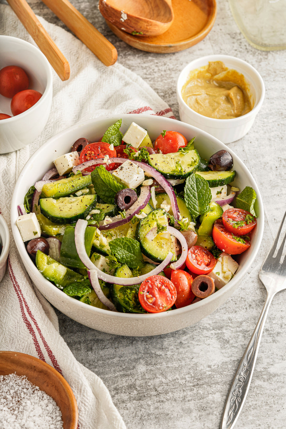 Greek salad in a white bowl with dressing ingredients in background.