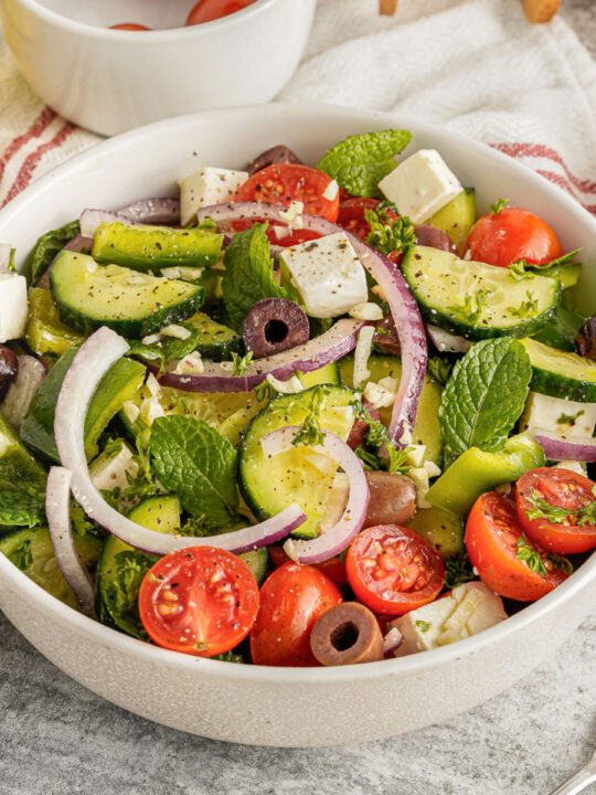 Fresh salad in a white bowl with greek dressing.