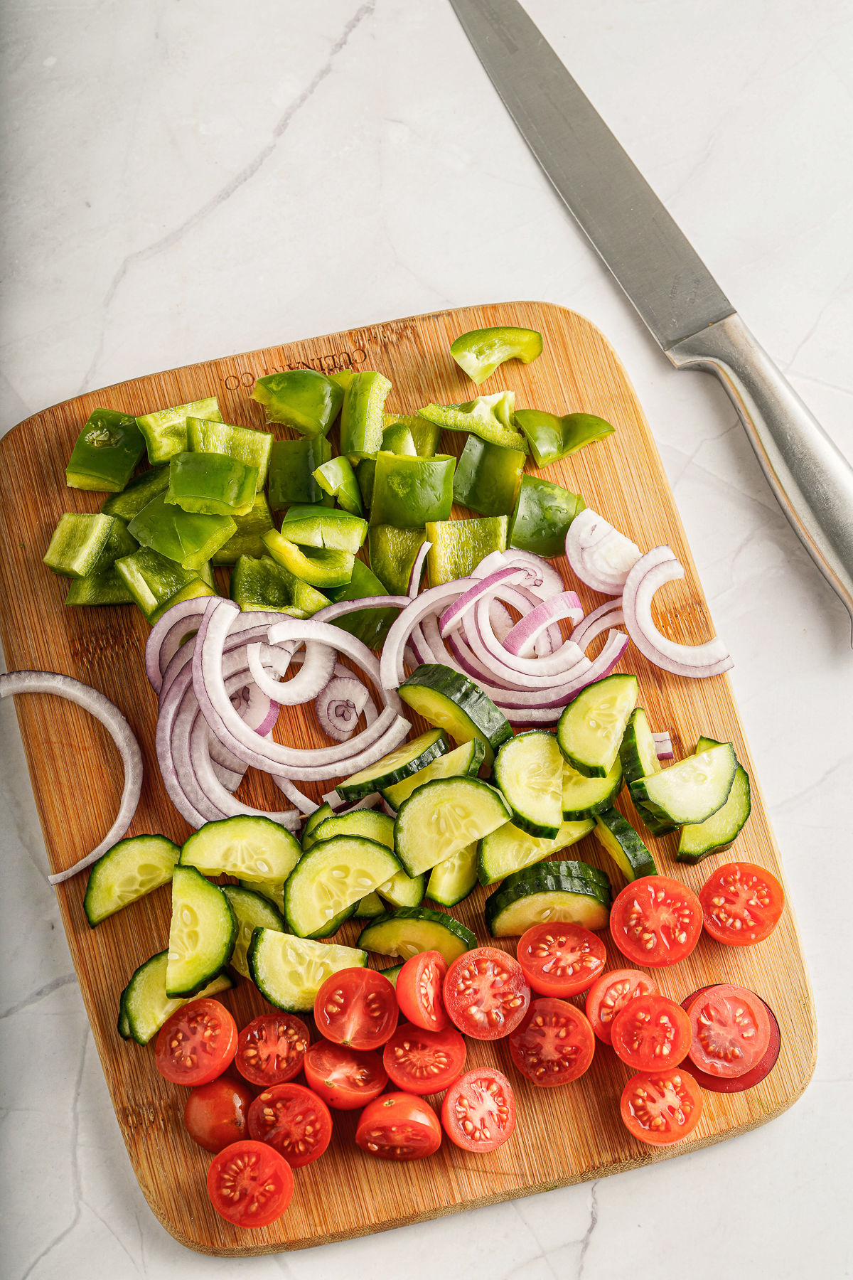 Chopped vegetables on a wooden cutting board for greek salad.