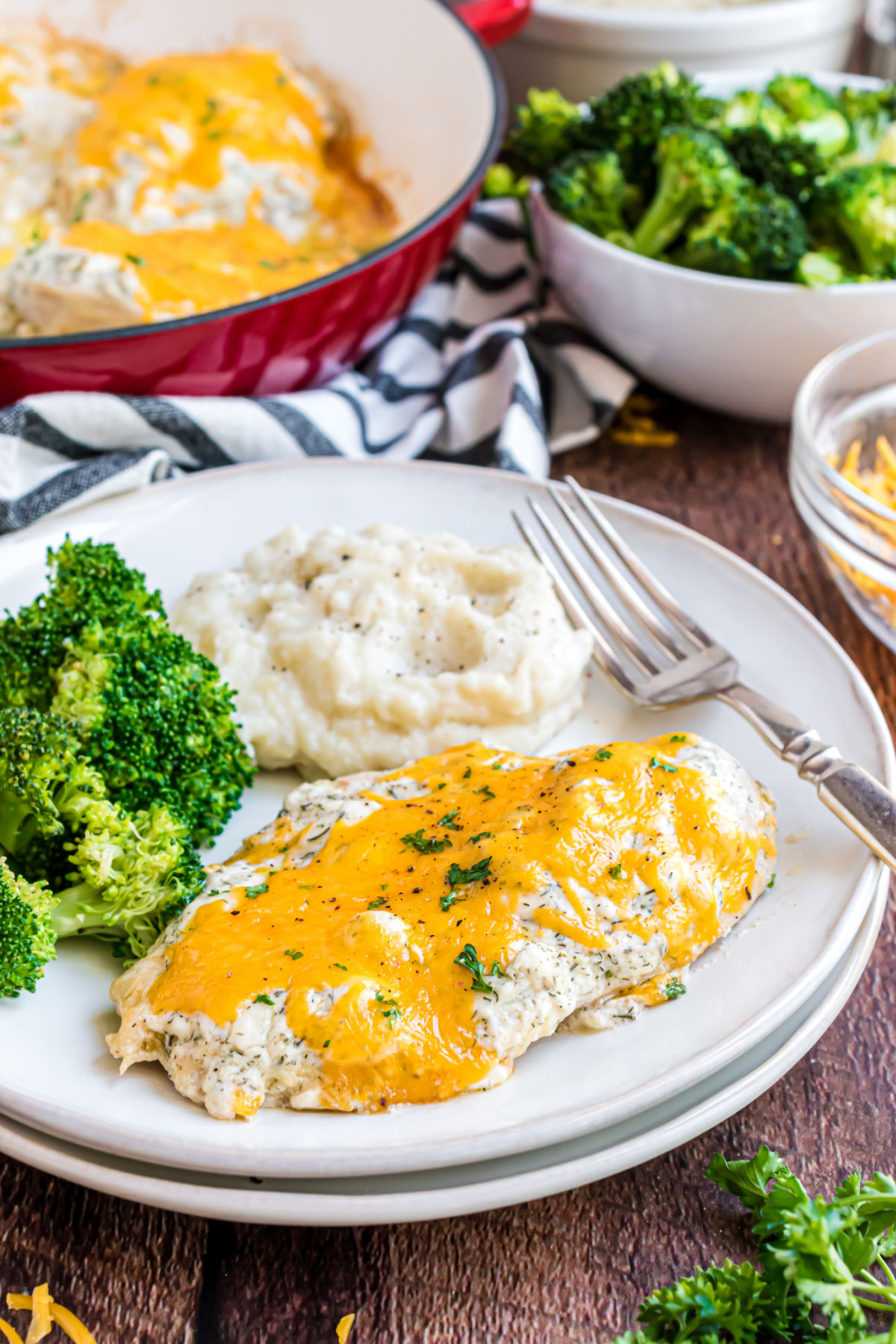 Baked chicken with low carb ranch dressing and cheese on a plate served with broccoli and mashed cauliflower.