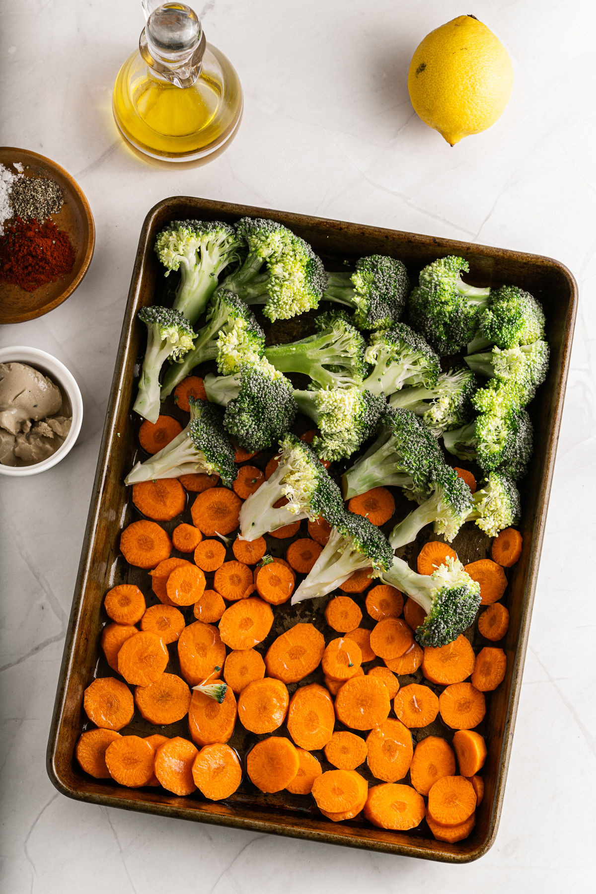 Broccoli and carrot slices on cookie sheet for roasting.