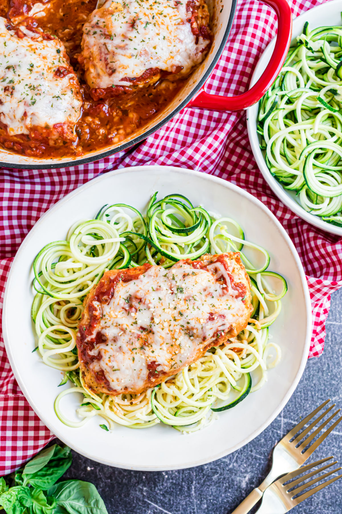 Chicken parmesan served over a plate of zoodles.