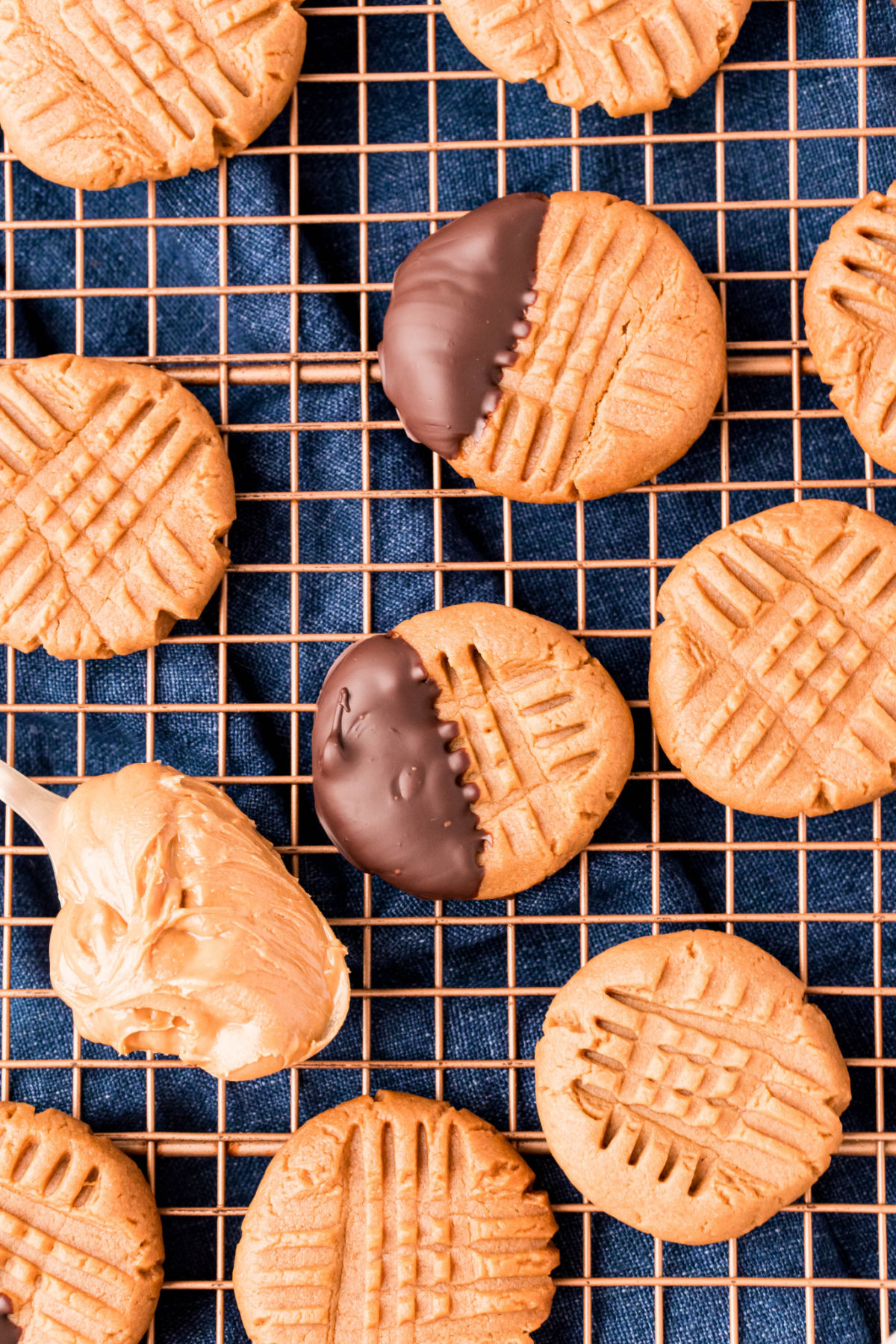 Sugar free peanut butter cookies on a wire rack, some dipped in sugar free chocolate.