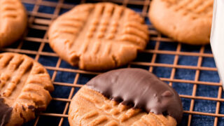 Sugar free chocolate dipped keto peanut butter cookies on wire rack.