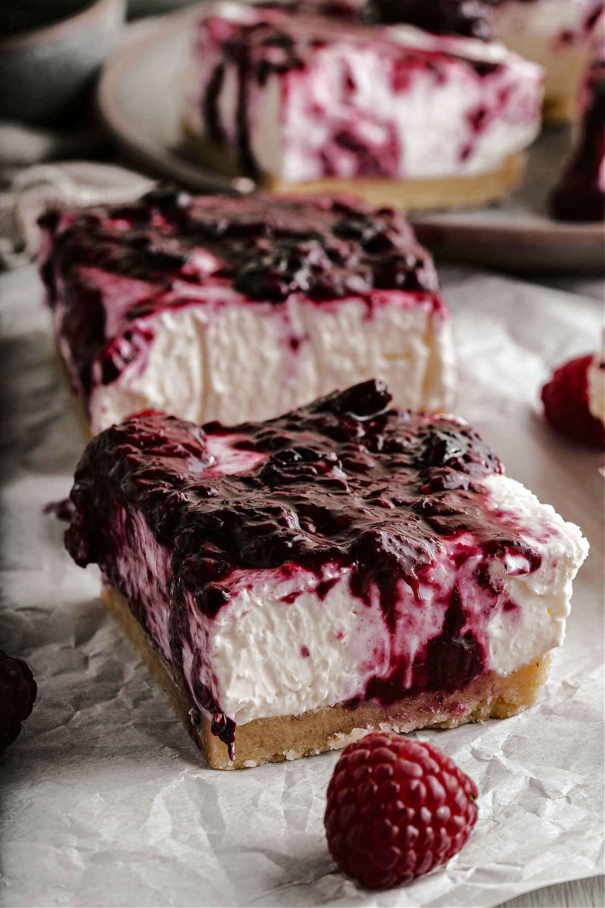 No bake cheesecake bars with a berry topping on parchment paper.
