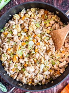 Chicken fried rice in cast iron skillet with cauliflower rice.