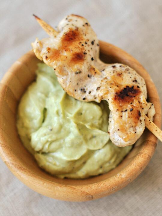 Greek seasoned grilled chicken on skewer with avocado tzatziki.