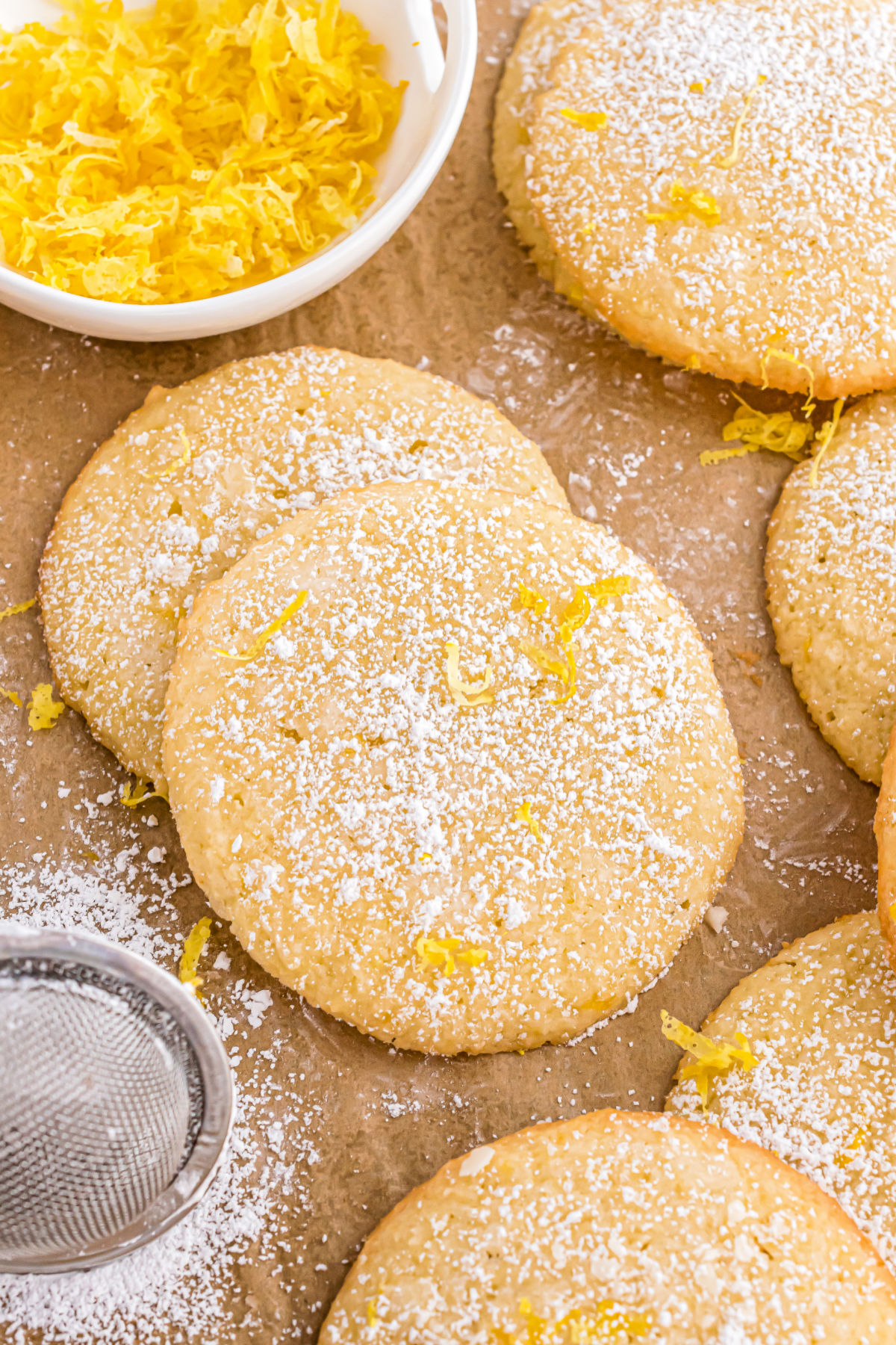 Lemon cookies on parchment paper and dusted with powdered sugar.