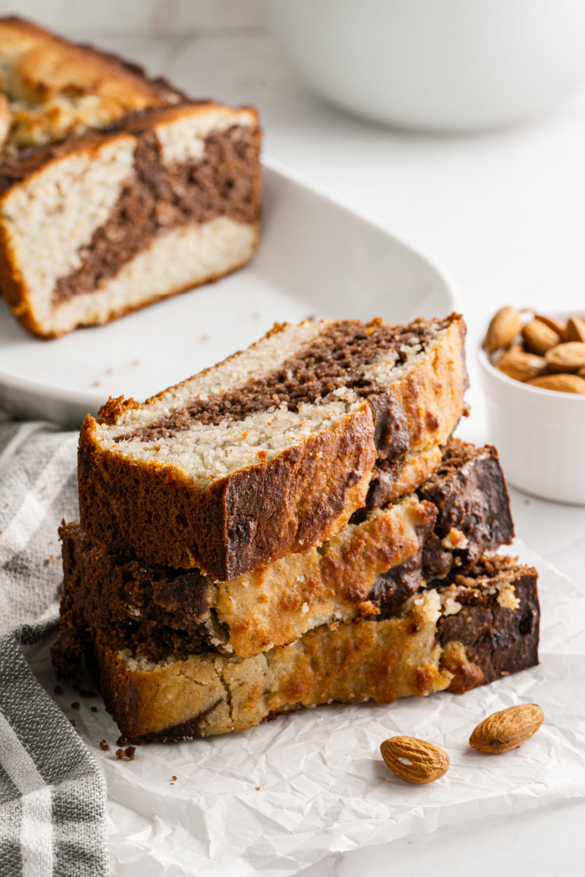 Three slices of sugar free banana bread stacked on plate.