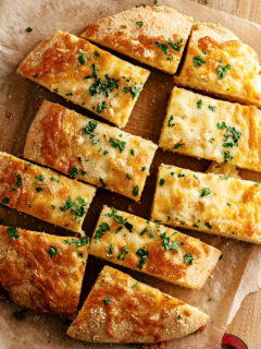 Keto gluten free garlic bread on parchment paper cut into rectangles.