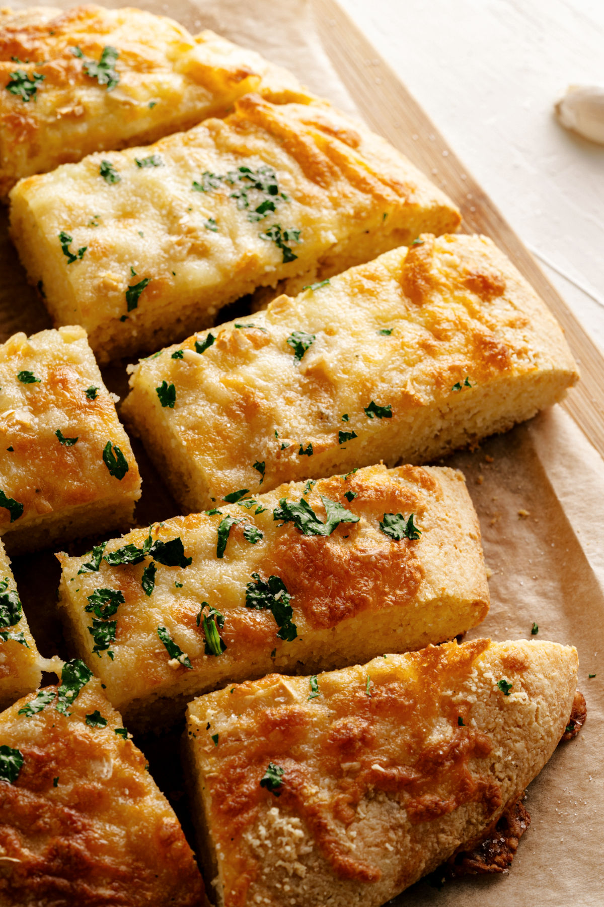 Parchment paper with gluten free garlic bread cut into pieces.