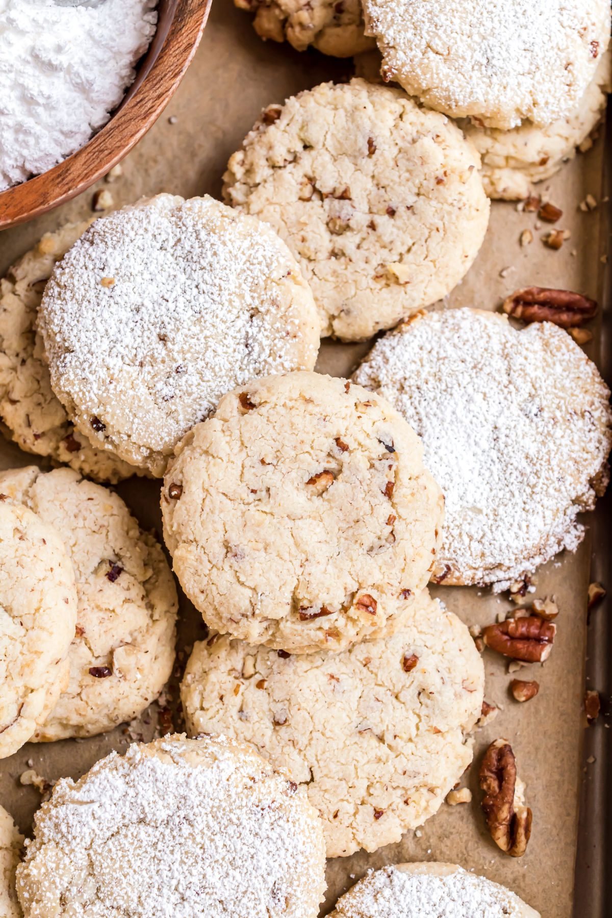Pecan sandies stacked on a piece of parchment paper.