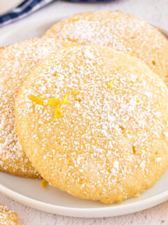 Three lemon cookies on a white dessert plate.