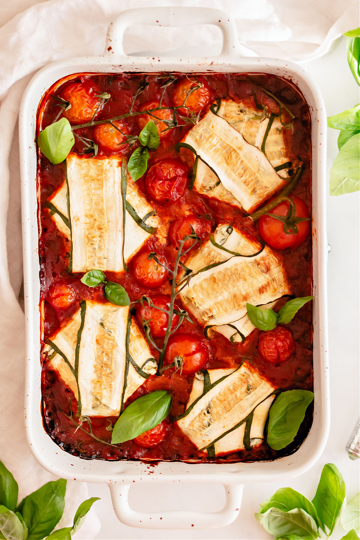 Zucchini rolled up with cheese and marinara sauce in white baking dish.