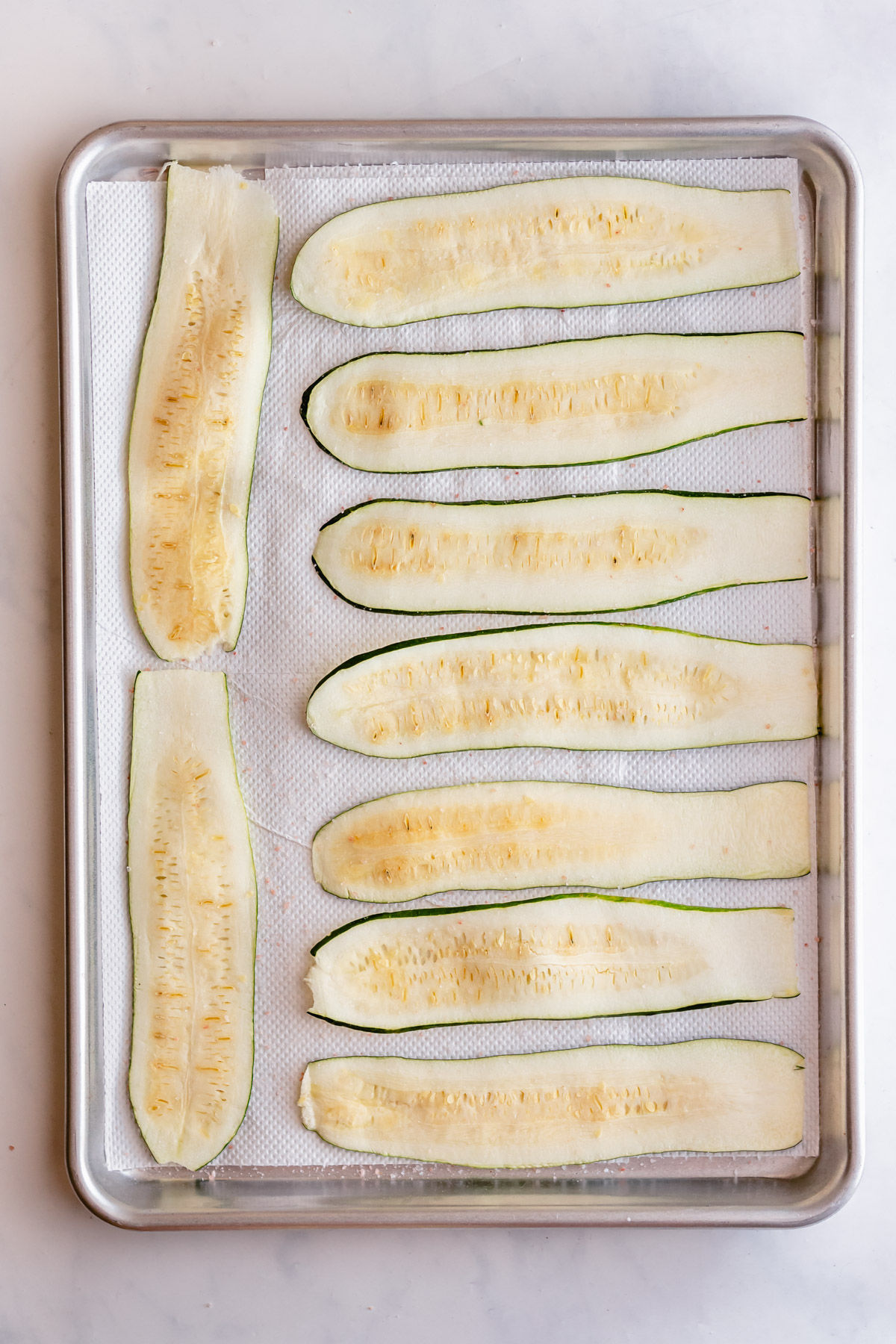 Zucchini strips on paper towel lined baking sheet and salted to remove moisture.
