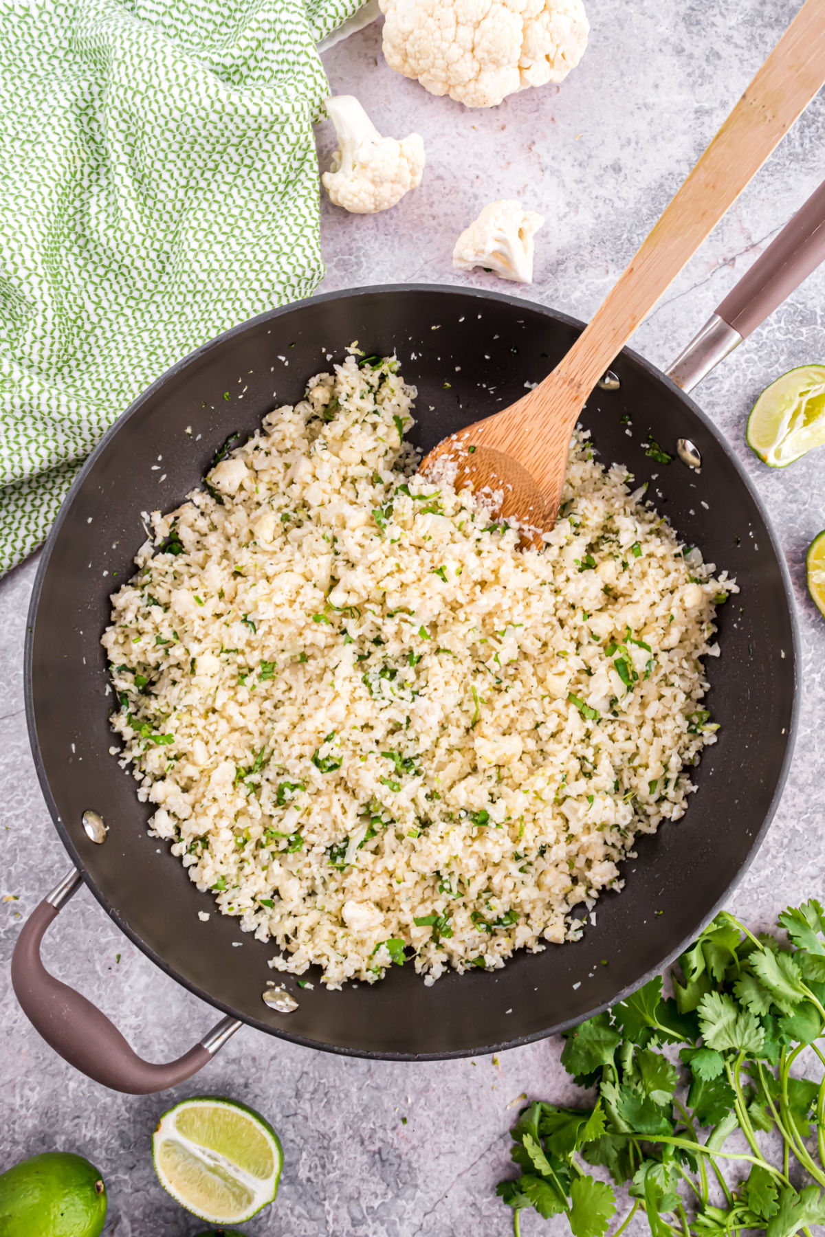 Skillet cooking cauliflower rice with cilantro and lime juice.