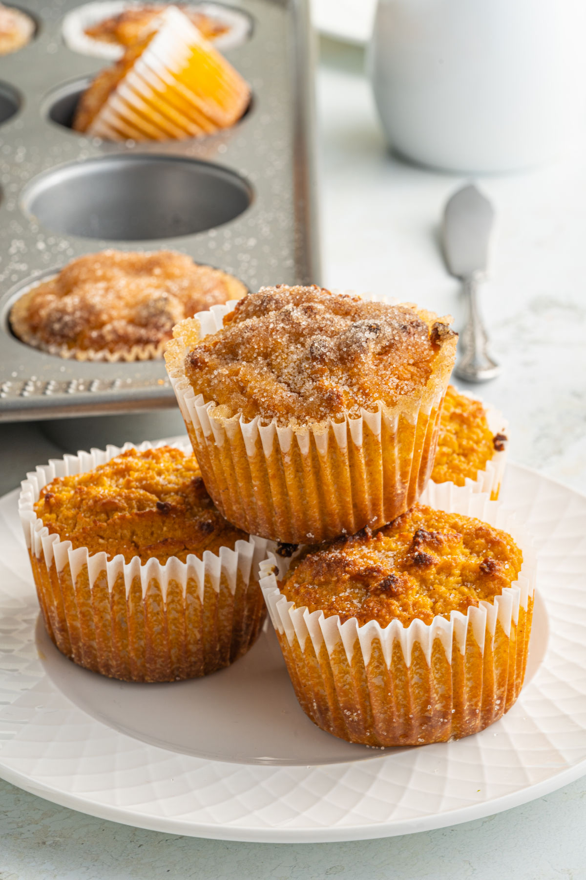 Stack of three pumpkin muffins in white wrappers.