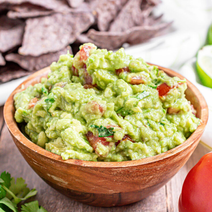 Wooden bowl with chunky guacamole and blue corn tortilla chips.
