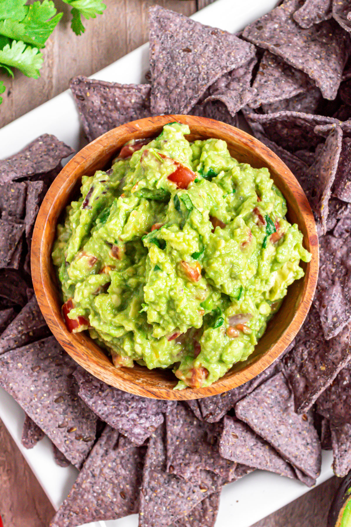 Guacamole in wooden bowl served with blue corn chips.