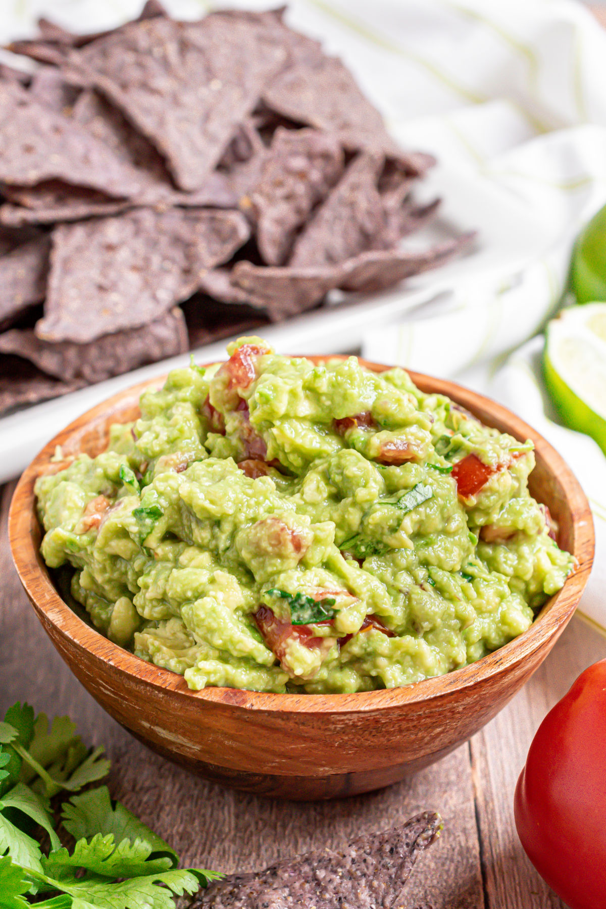 Chunky guacamole in a wooden bowl.