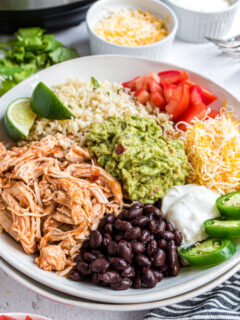 A white bowl with chicken taco ingredients, including cauliflower rice, beans, guacamole, and more.
