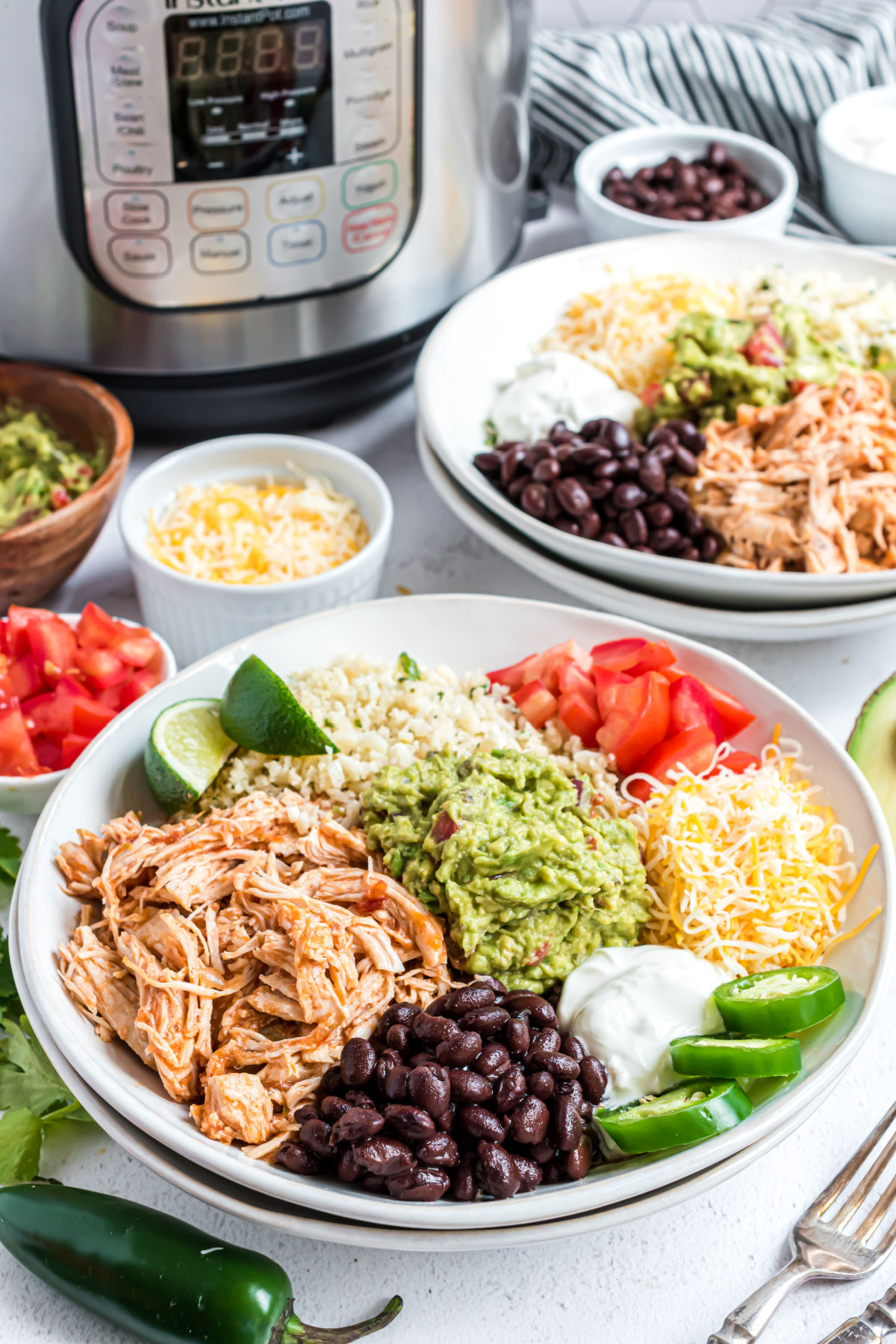 Chicken taco bowl with cheese, guacamole, black beans assembled in a white bowl with Instant Pot in background.