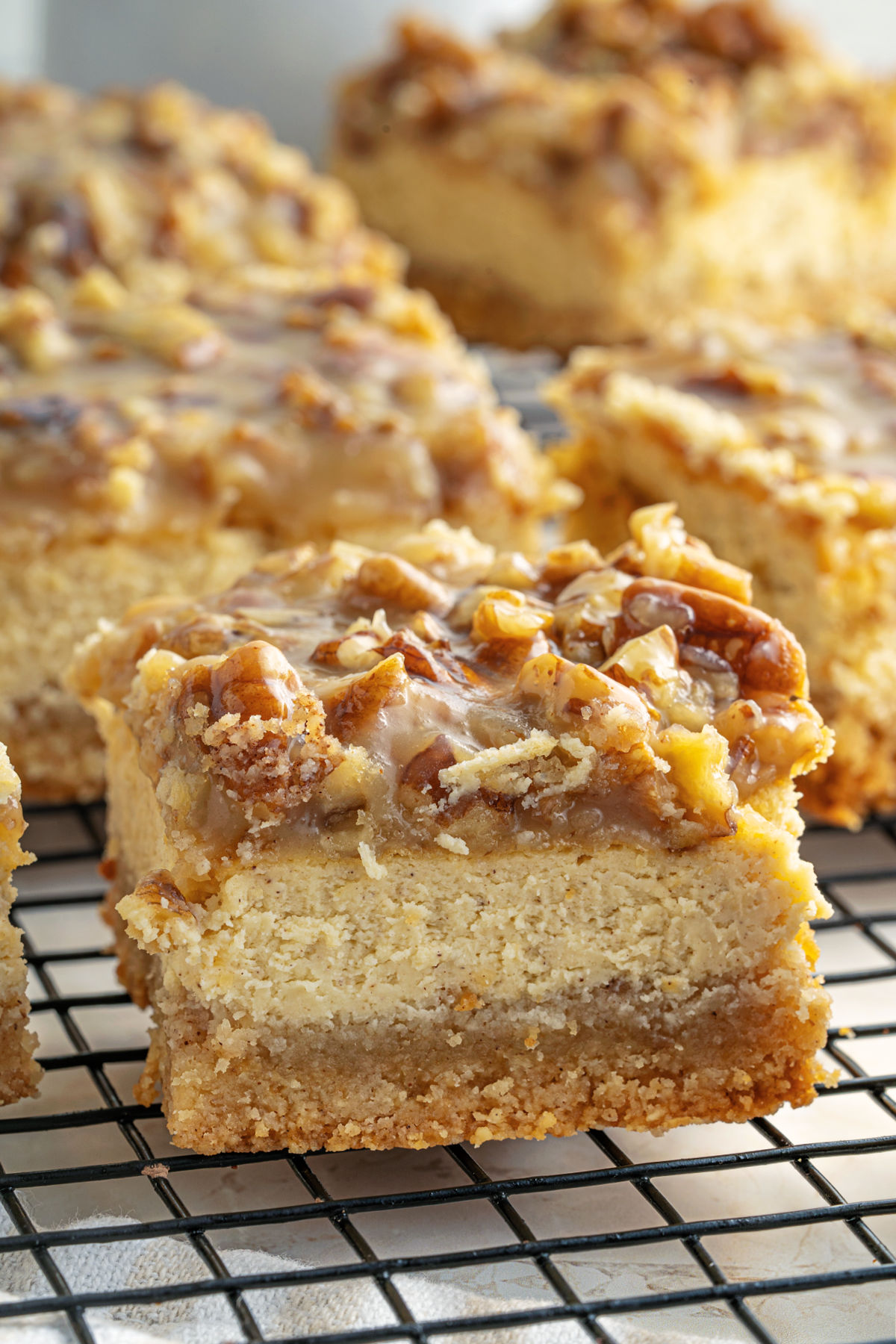 Squares of pecan pie cheesecake bars on a wire rack.